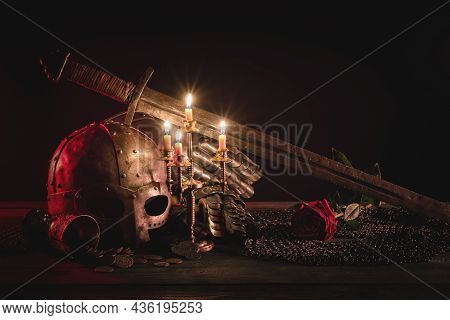 Medieval Armor, Helmet, Knight Sword And Red Rose Flowers On The Table In The Light Of Burning Candl