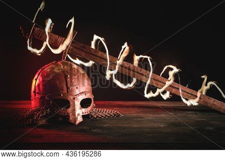 Medieval Knight Helmet And Ancient Sword In The Fire On The Table Background.