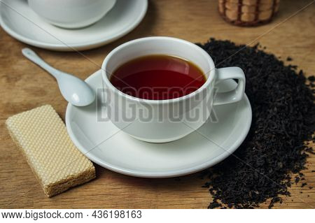 A Cup Of Tea Next To Black Loose Tea. Cup Of Strong Black Tea On Wooden Background