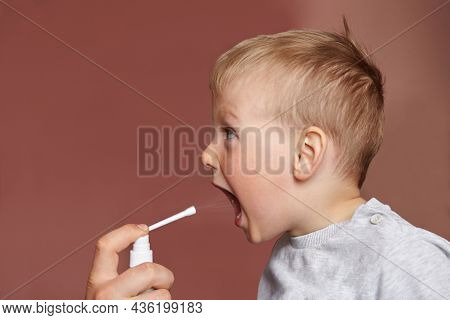 The Child Receives Medication Through A Mouth Spray For A Sore Throat. A Small Boy Sprays A Spray In