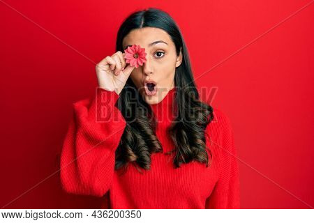 Young hispanic woman holding flower over eye scared and amazed with open mouth for surprise, disbelief face