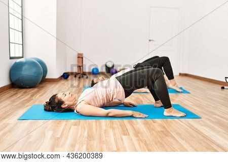 Mature hispanic couple doing excersice and stretching at yoga room. Two adult people doing pilates and flexibility workout