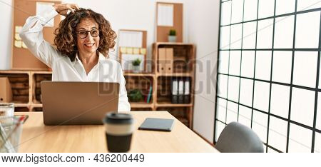 Middle age hispanic woman working at the office wearing glasses confuse and wonder about question. uncertain with doubt, thinking with hand on head. pensive concept.