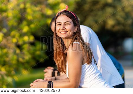 Woman Smiling To The Camera While Resting In A Railing Outdoors With His Friends