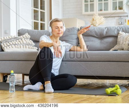 Senior Woman With Closed Eyes In Headphones Listen Music In Living Room. Relax After Exercising Fitn