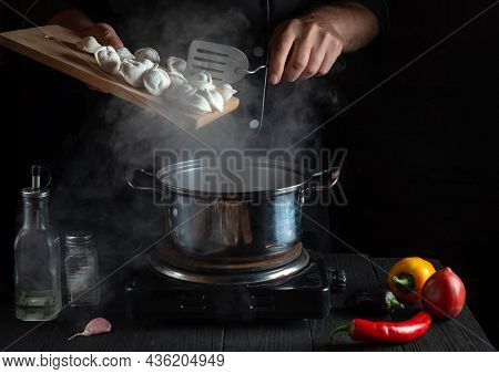 The Professional Chef Cooks Meat Dumplings In A Saucepan In The Restaurant Kitchen. Close-up Of Hand