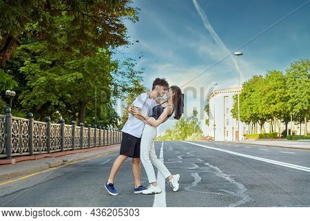 Young Guy With A Girl Hugging In The Summer In The City On The Roadway.