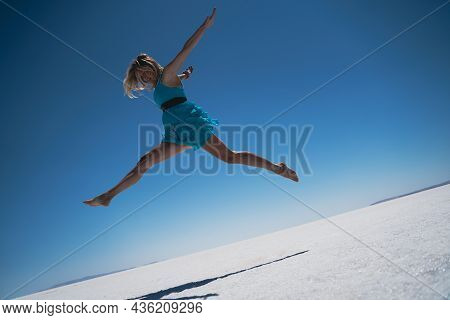 Side View Of Blonde Beautiful Caucasian Young Woman Dressed In Blue Jumping A Giant Leap Barefoot On