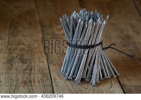A Stack Of Nails, Tied With A Rope In A Pile, On A Wooden Table Close-up