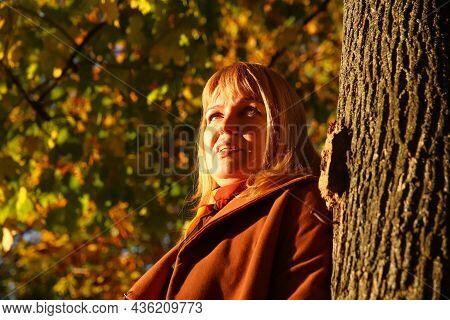 Portrait Of Pretty Caucasian Blonde Woman In Colorful Yellow Maple Autumn Park. Bright Stylish Woman