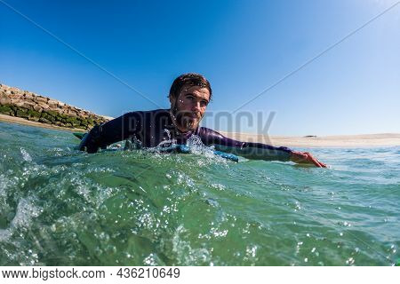 Bodyboarder Rowing Over The Water