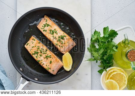 Juicy Salmon Fillet Fried On Pan With Parsley, Oil Olive And Lemon. Flavorful Pescetarian Meal. Heal