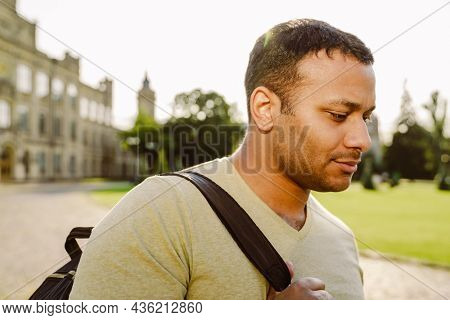 Middle eastern student man with backpack standing by university outdoors
