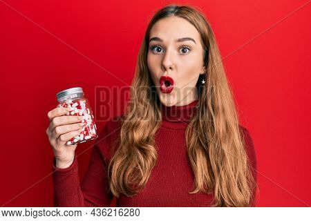 Young blonde woman holding jar of pills scared and amazed with open mouth for surprise, disbelief face