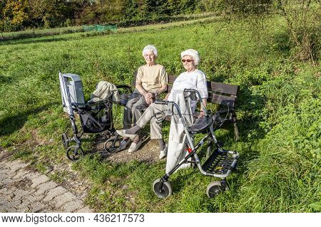 Schwalbach, Germany - October 19, 2014: Elderly Female Couple Enjoys The Spring Sun While Sitting On
