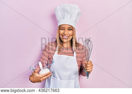Beautiful hispanic woman holding bread dough and whisk winking looking at the camera with sexy expression, cheerful and happy face.