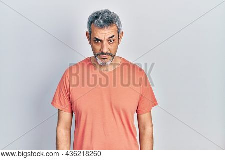 Handsome middle age man with grey hair wearing casual t shirt skeptic and nervous, frowning upset because of problem. negative person.