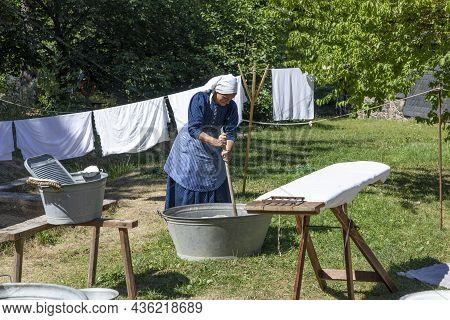 Neu Anspach, Germany - August 6, 2020: Woman In Traditional Costume Cleans The Laundry In The Old Tr