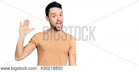 Hispanic man with beard wearing casual t shirt waiving saying hello happy and smiling, friendly welcome gesture