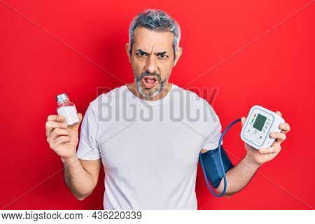 Handsome middle age man with grey hair using blood pressure monitor holding salt in shock face, looking skeptical and sarcastic, surprised with open mouth