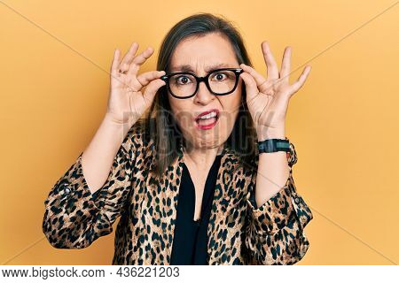 Middle age hispanic woman wearing business clothes and holding glasses in shock face, looking skeptical and sarcastic, surprised with open mouth