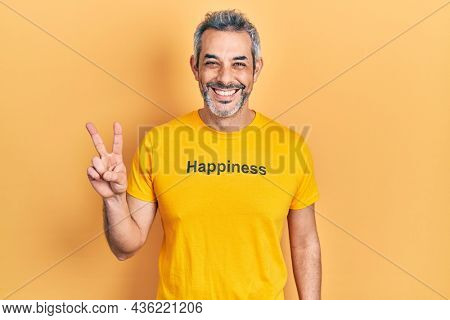Handsome middle age man with grey hair wearing t shirt with happiness word message smiling with happy face winking at the camera doing victory sign. number two.