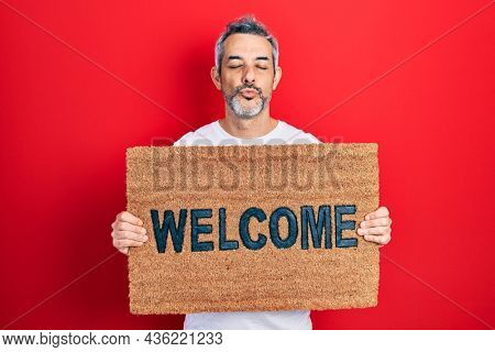Handsome middle age man with grey hair holding welcome doormat looking at the camera blowing a kiss being lovely and sexy. love expression.