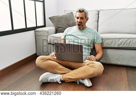 Middle age hispanic man using laptop sitting on the floor at the living room in shock face, looking skeptical and sarcastic, surprised with open mouth