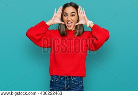 Beautiful brunette woman wearing casual winter sweater smiling cheerful playing peek a boo with hands showing face. surprised and exited