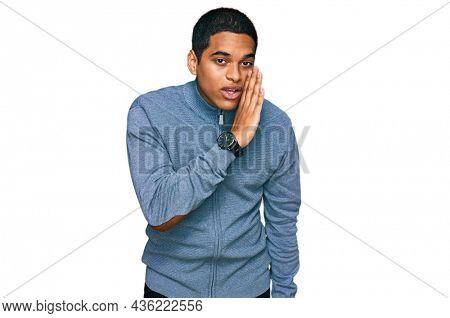 Young handsome hispanic man wearing casual sweatshirt hand on mouth telling secret rumor, whispering malicious talk conversation