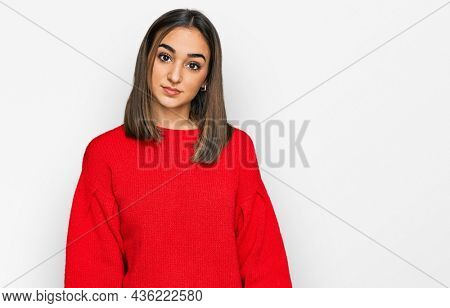 Beautiful brunette woman wearing casual winter sweater relaxed with serious expression on face. simple and natural looking at the camera.