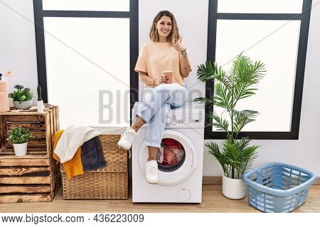Young hispanic woman drinking coffee waiting for washing machine at laundry room doing happy thumbs up gesture with hand. approving expression looking at the camera showing success.