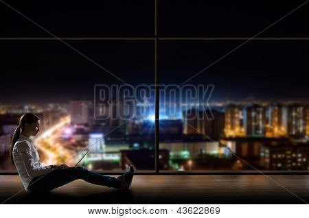 young woman sitting with a laptop by the window