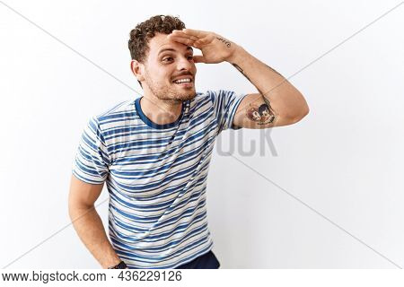Handsome young man standing over isolated background very happy and smiling looking far away with hand over head. searching concept.