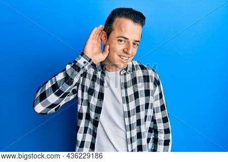 Handsome young man wearing casual shirt smiling with hand over ear listening and hearing to rumor or gossip. deafness concept.