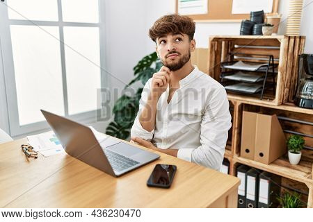 Young arab man working using computer laptop at the office serious face thinking about question with hand on chin, thoughtful about confusing idea