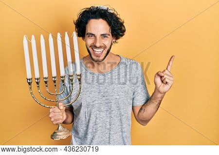 Handsome hispanic man holding menorah hanukkah jewish candle smiling happy pointing with hand and finger to the side