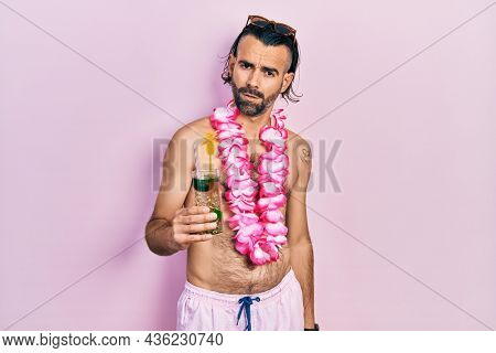 Young hispanic man wearing swimsuit and hawaiian lei drinking tropical cocktail in shock face, looking skeptical and sarcastic, surprised with open mouth