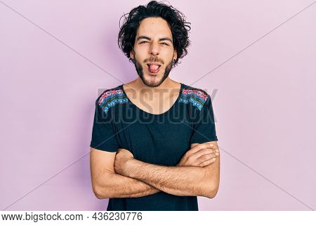 Handsome hispanic man with arms crossed gesture sticking tongue out happy with funny expression.