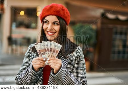 Young hispanic woman smiling happy holding russian ruble banknotes at the city.