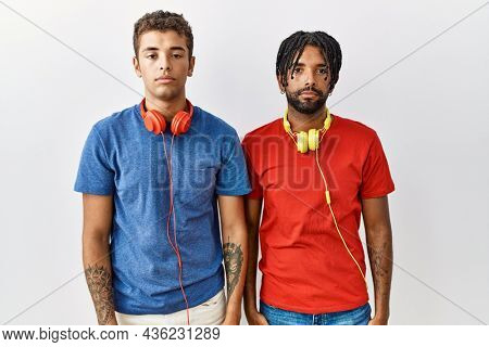 Young hispanic brothers standing over isolated background wearing headphones relaxed with serious expression on face. simple and natural looking at the camera.