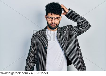 Young arab man with beard wearing glasses confuse and wonder about question. uncertain with doubt, thinking with hand on head. pensive concept.