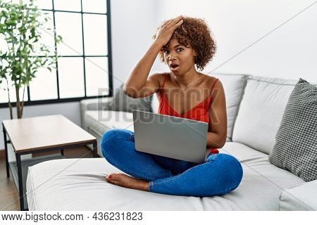 Young african american woman sitting on the sofa at home using laptop surprised with hand on head for mistake, remember error. forgot, bad memory concept.