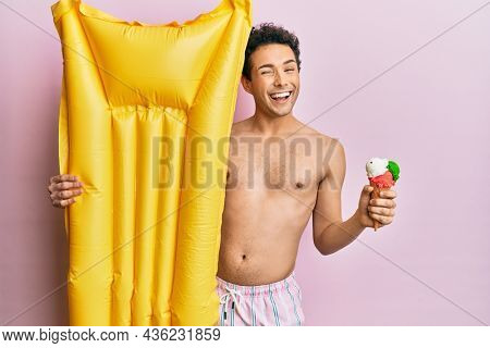 Young handsome man wearing swimsuit holding summer mattress float and icecream winking looking at the camera with sexy expression, cheerful and happy face.