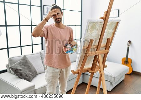 Young hispanic man with beard painting on canvas at home worried and stressed about a problem with hand on forehead, nervous and anxious for crisis