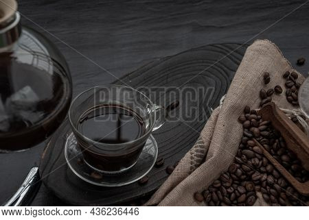 Coffee Style, Cup Of Coffee And Coffee Beans Roating With Old Wooden Scoop And Coffee Beans Around O