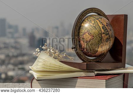 Journey And Learning Concept Background. Globe And Stack Of Books With A Sky Background. Copy Space.