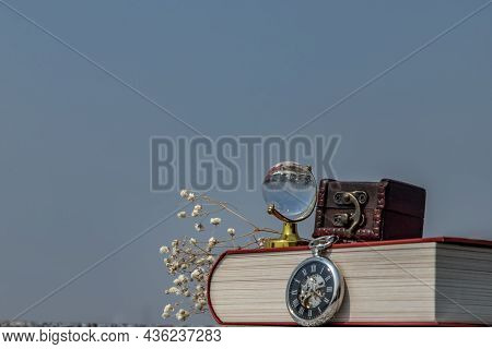 Journey And Learning Concept Background. Crystal Globe, Pocket Watch And Stack Of Books With A Sky B