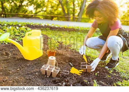 Beautiful Young Woman With Afro Hairstyle Working At Her Garden At Sunset Spring Time Outdoors
