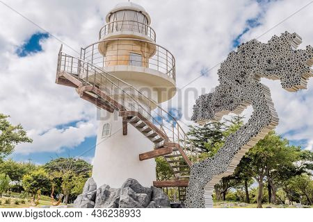 Uljin-eup, South Korea; September 19, 2021: Lighthouse On Cliff In Park Overlooking Hubo Seaport Und
